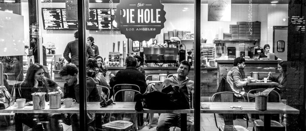 Black and white picture, looking through the glass at customers in Pie Hole Restaurant.